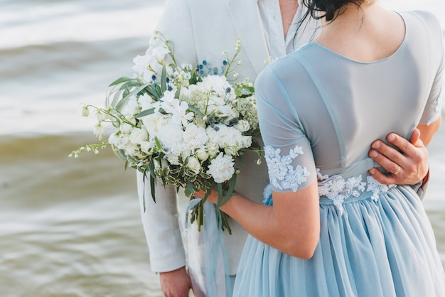Groom having his hand on his bride's waist, standing on a beach. bride is holding a bouquet.