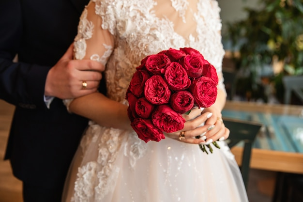 Groom holding bride's hand, bride with red bouquet