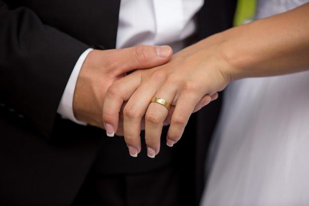 新郎が結婚式や婚約指輪で花嫁の手を握って