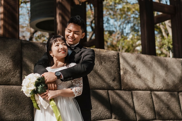 Groom holding the bride with bouquet of flowers outdoors