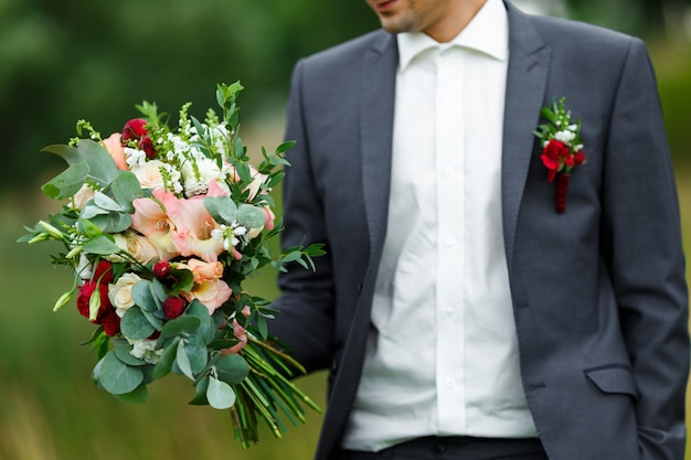 Groom holding in hands a trendy bridal wedding bouquet of flowers