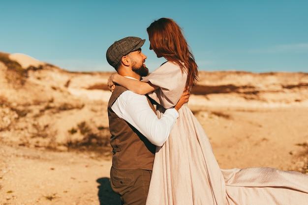 Жених держит свою невесту на руках возле красивого пейзажа