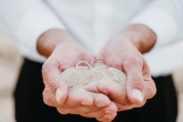 Groom holding sand and rings in his hands