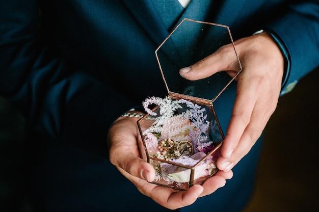 손바닥에 상자에 결혼 반지를 들고 신랑, 파란색 정장에 신랑, 남자는 반지를 잡아. 약혼.