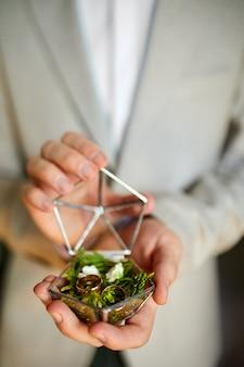장식 손 안에 결혼 반지를 들고 신랑 식물과 소박한 상자를 만든
