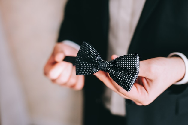 新郎は蝶ネクタイを手に持ち、服を着て結婚式の準備をします。新郎の朝の準備。ウェディングアクセサリー。人、ビジネス、ファッション、ウェアのコンセプト。