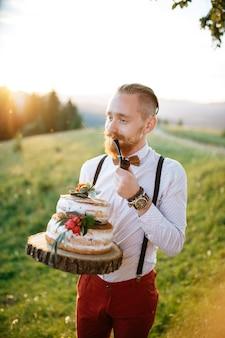 Жених держит деревянный поднос с свадебным торт и трубой