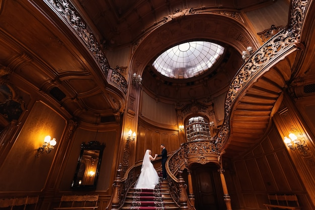 The groom holds the bride by the hand and they climb on wooden carved stairs