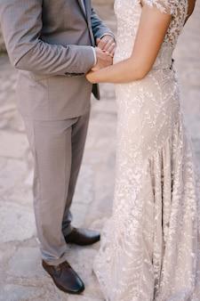 新郎は彼の手で花嫁の手を握ります