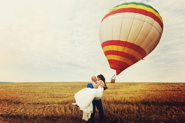 Groom holds bride in his arms while wind blows away air balloon