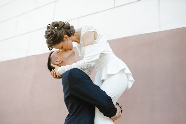 Groom holds bride on his hands and kisses her