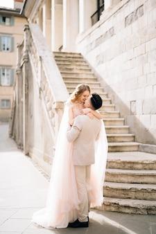 新郎は、ベルガモイタリアの古い建物の階段の近くで彼の腕に花嫁を保持します