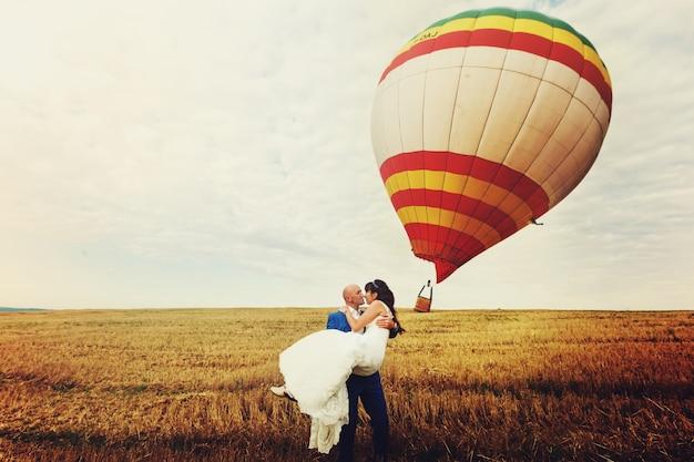 風が風船を吹き飛ばす間、新郎は腕の中に花嫁を保持する