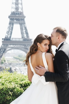 Groom holds bride's back tender standing before eiffel tower in paris