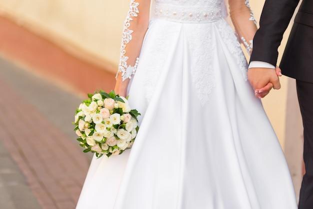 Жених держит руку невесты, гуляя с ней по улице