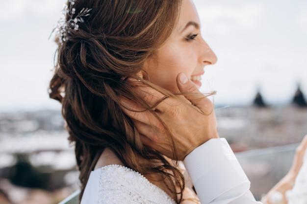 Жених держит невесту нежно стоять на крыше с большим летним городским пейзажем вокруг них