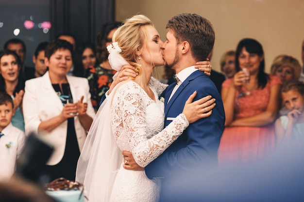Groom holds bride tightly while they kiss in the crowd of guests