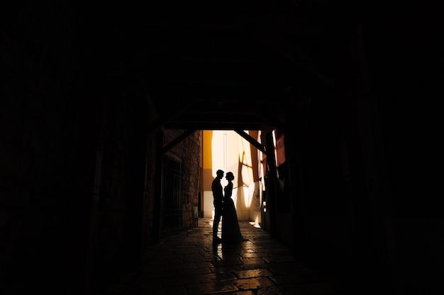 Жених держит невесту за руки, стоя в тени двора старого дома в шибенике, хорватия