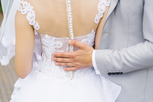 The groom holds the hand on the back of the bride with beautiful wedding dress