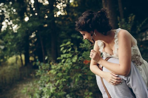 Lo sposo tiene la sua sposa tra le braccia da qualche parte nella natura