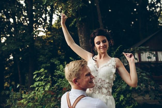 新郎は自然のどこかで彼の腕に彼の花嫁を保持します