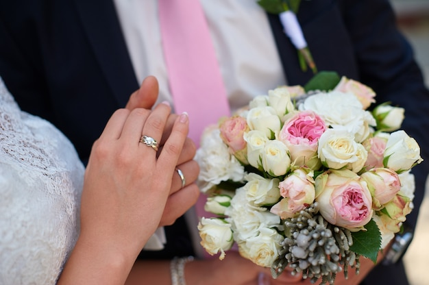 Groom holds his brides hand and a wedding bouquet close up