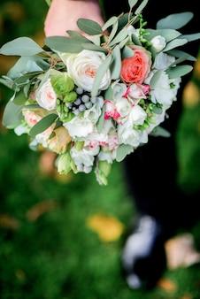 Жених держит в руке небольшой свадебный букет