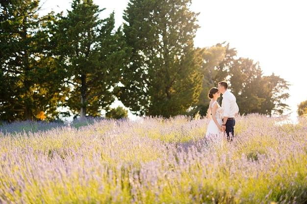 Жених держит руку невесты в белом платье и целует ее в лоб на фоне лавандового поля.