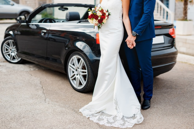 新郎は、舗装スラブの上に立っている間、花の花束で花嫁の手を握ります