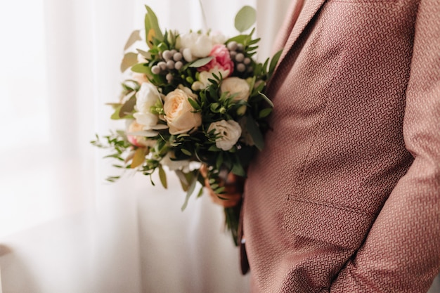 The groom holds a wedding bouquet in his hands