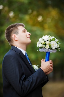 The groom holds a wedding bridal bouquet in hand and looks up