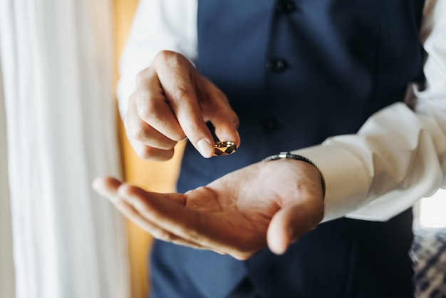 Groom holds wedding ring standing before the window in a hotel r