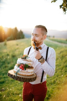 Groom holds a wooden tray with wedding cake and a pipe