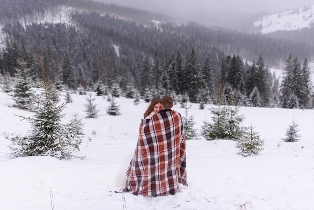 Groom hugging his bride under the blanket in the winter