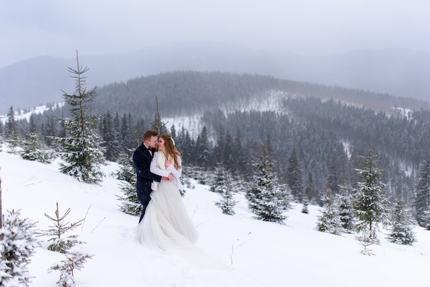 Groom hugging his bride in the snowy forest