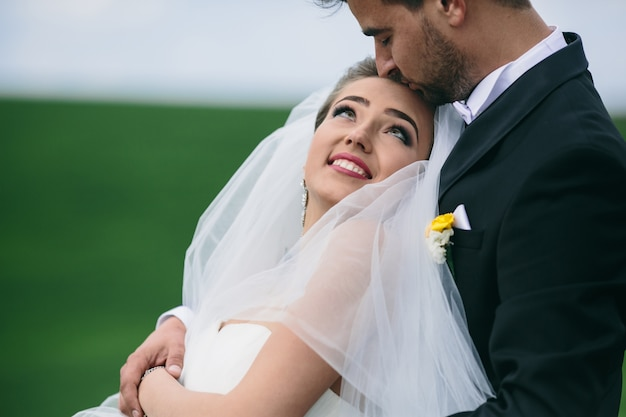 Groom hugging his wife and kissing her forehead