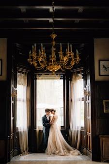 Жених обнимает невесту на фоне больших окон