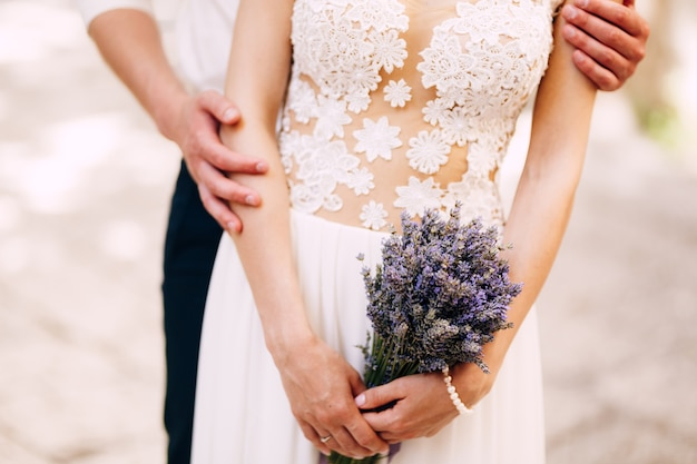 Groom hugs bride from behind in a white lace dress with a lavender bouquet in her hands closeup