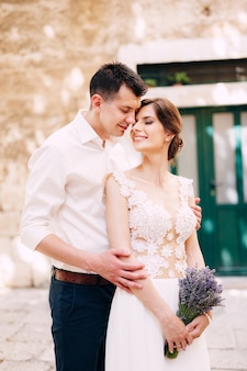 Groom hugs bride from behind in a white lace dress with a lavender bouquet in her hands portrait