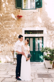 Groom hugs bride from behind in a white lace dress with a lavender bouquet standing in the courtyard