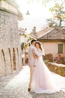 新郎は花の花束と美しいドレスで花嫁を抱きしめます