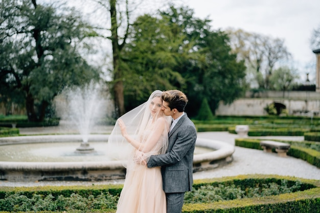 新郎は後ろからベールで花嫁を抱きしめ、庭の肩で彼女にキスします