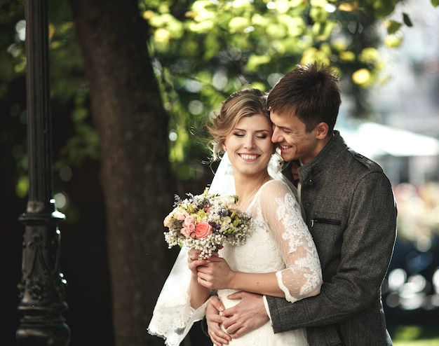 Жених обнимает невесту в парке
