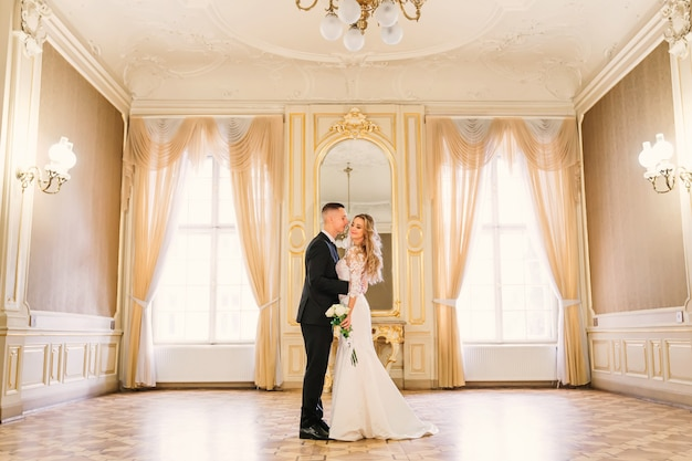 The groom hugs the bride and she closes her eyes and holds the wedding bouquet. spacious room with large windows and a mirror.