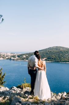 Groom hugs bride in a white dress while standing on the rocky shore above the sea against the