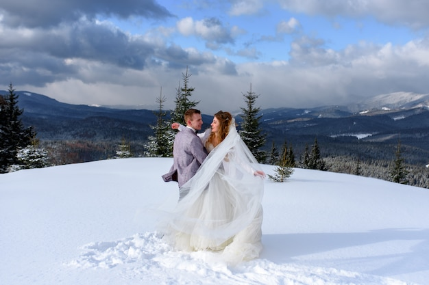 Groom hugs his bride against the backdrop of snow-capped mountains. winter wedding photo.