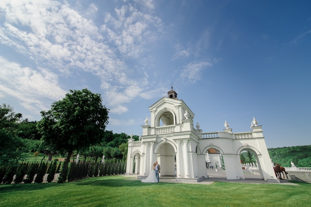 Groom hugs his bride on the green grass against white arch. taken from a far angle.