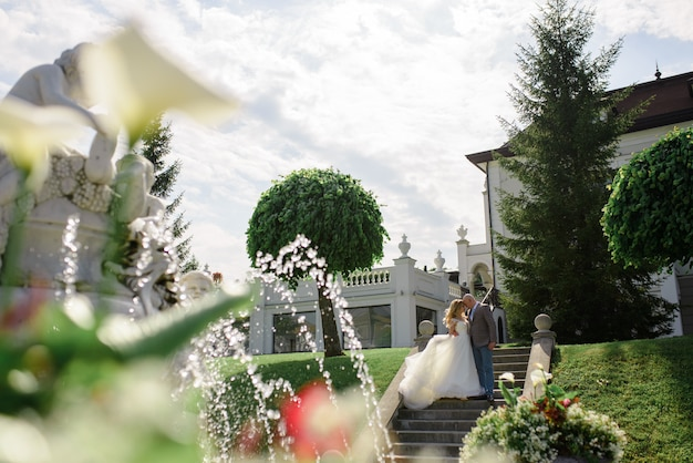 Groom hugs his bride. shot through a fountain.