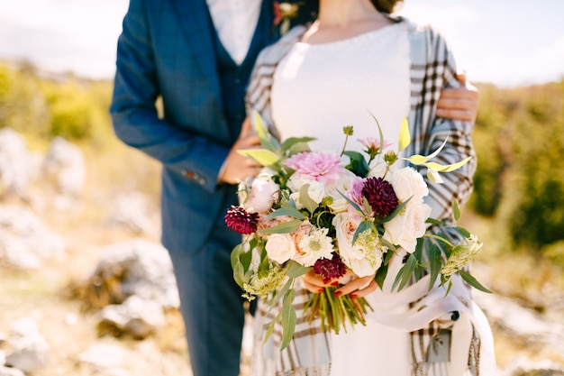 Groom hugs the shoulders of bride in a checkered shawl with a beautiful bouquet of flowers
