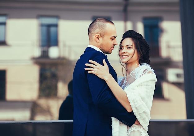 Groom hugs stunning bride